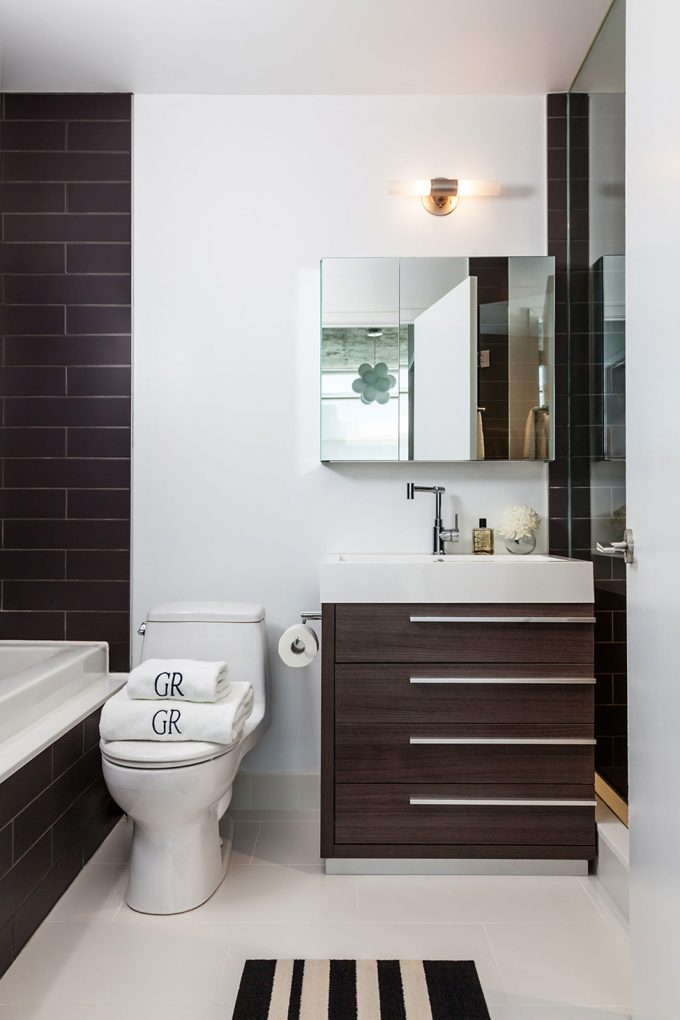Modern Bathroom With Brown And White Theme Using Brown Vanity And Brown Wall Also White Rugs