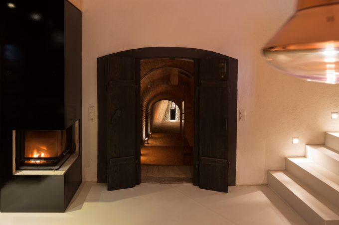 Rustic Black Wooden Door And A Tunnel To The Wine Cellar With Brick Wall Decor