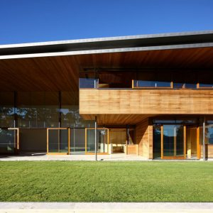 Awesome Green Turf With Wooden House Exterior And Large Glass Walls For Contemporary House Design