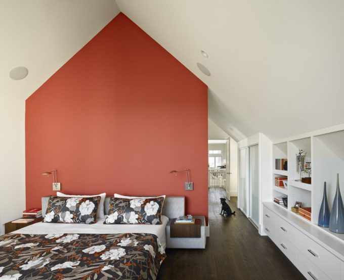 Beautiful Attic Bedroom With Orange Wall Partition And White Bedding With Floral Blanket Plus White Shelves