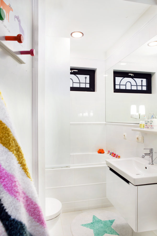 Beautiful Kid's Bathroom With White Tile And White Hanging Bathroom Vanity With Apron Sink