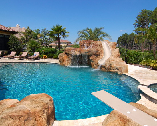 Mediterranean Pool With Fake Stone And Swimming Pool With Diving Boards Also Sun Bathring Area