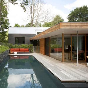 Minimalist Swimming Pool With Wooden Deck And Stone Wall Decor