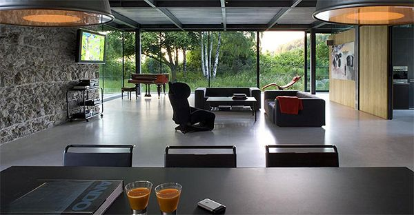 Modern Lounge Room With Black Fofa And Glass Windows Also Green Landscape View