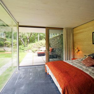 Natural Bedroom Design Using Wooden Wall And Natural Stone Like Floor Tile Also Floor To Ceiling Decor And King Size Bed