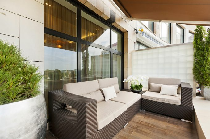 Relaxing Terrace View With Wicker Sofa With Chocolate Covers For Luxury Apartment Decorations
