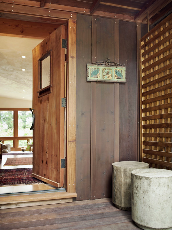 Rustic Entry Wirh Wooden Swing Door And Board Batten Wood Siding Also Soncrete Chairs
