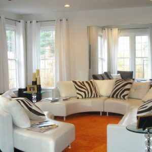 Simple White Living Room With Round Sectional Sofa And Orange Rugs Also Zebra Room Accessories Plus Glass End Table