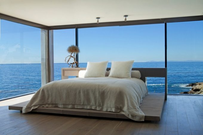 Superb Relaxing Bedroom Design With Glass Walls And Cozy White Bedding Plus Wooden Flooring