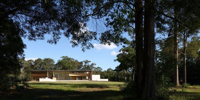 The Back Facade Of Spacy Wooden House With Large Lawn Surround With Green Lush Vegetation