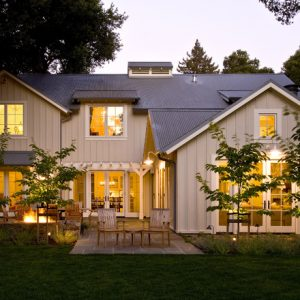 Traditional House With Board Batten Wood Siding And Wood Roof Also Warm Interior Lighting Plus Green Open Landscaping