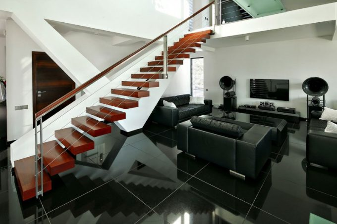 Wood Beams Staircase With Steel Handrailing And Black Glossy Floor And Black Sectional Sofa In Modern Living Room Design