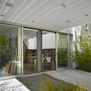 Work Space With Glass Wall And Family Room With Colorful Chairs And Book Shelves Plus Sliding Glass Door