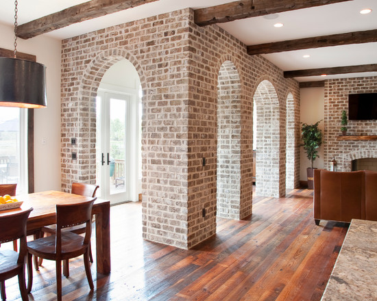 Traditional Living Room With Grey Brick Wall And Exposed Wood Floors Also Arched Door Trim