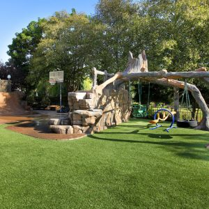 Amazing Backyard Design Ideas With Stacked Stones Ideas And Lawn Plus Surprising Outdoor Play Area With Swing Sets And Basketball Court Plus Big Trees Also Low Fence