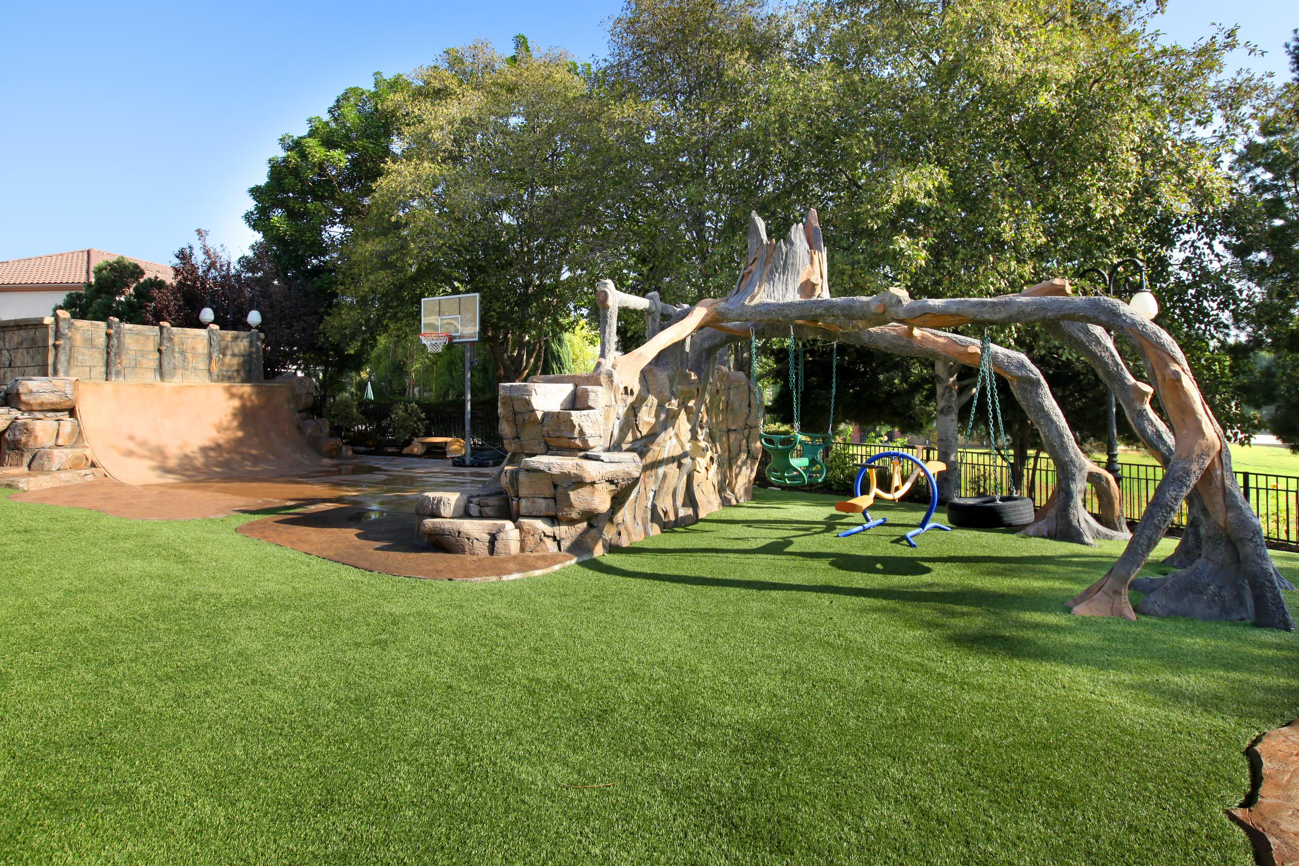Exciting Backyard Design Ideas with Swing Sets: Amazing Backyard Design Ideas With Stacked Stones Ideas And Lawn Plus Surprising Outdoor Play Area With Swing Sets And Basketball Court Plus Big Trees Also Low Fence