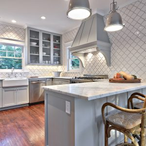 Arabesque Tile With Industrial Pendant Lighting Also Recessed Lighting And Farmhouse Sink With Wood Flooring Also Crown Molding Plus Under Cabinet Lighting For Traditional Kitchen