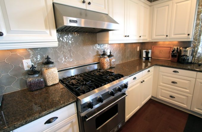 Arabesque Tile With Stainless Steel Range Hood Also Under Cabinet Lighting And White Kitchen Cabinets With Gas Stove Also Kitchen Knobs Plus Dark Wood Floors For Traditional Kitchen