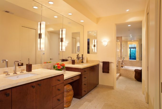 Bathroom Vanity Cabinets With Double Sink Vanity And Vanity Mirror For Contemporary Bathroom Design With Wall Sconce And Towel Bar Plus Bathtub Also Ceiling Lights