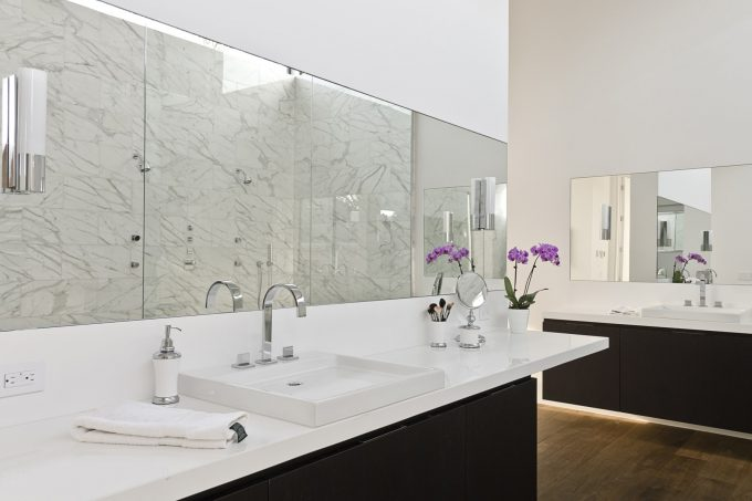 Beautiful Orchid On Floating Cabinets With White Clean Countertop Plus Sink And Dornbracht Also Vertical Bathroom Mirror In Modern Bathroom Ideas Plus Wall Sconce And Wood Flooring