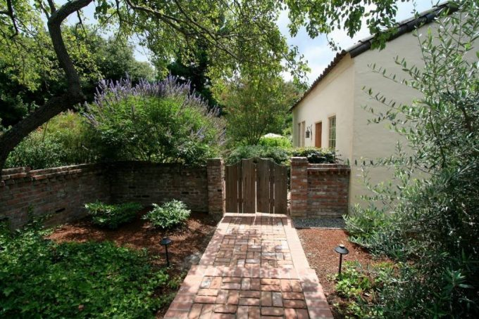 Brick Fence With Wooden Gates And Brick Paving For Mediterranean Landscape Design With Brick Walkway And Outdoor Lighting Plus Fresh Lavender Also White Exterior Wall Decor