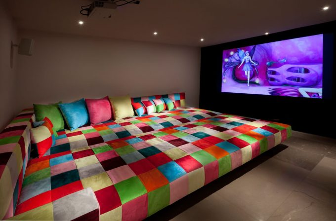 Bright Colors With Patchwork For Oversized Couches As Daybed Plus Decorative Pillows In Eclectic Home Theater With Ceiling Lighting Plus Projector And Stone Flooring
