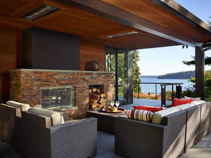 Captivating Stone Fireplace In Contemporary Deck With Infratech On Wood Ceiling And Railing Plus Decorative Pillows On Woven Armchairs Also Woven Coffee Table Plus Water View