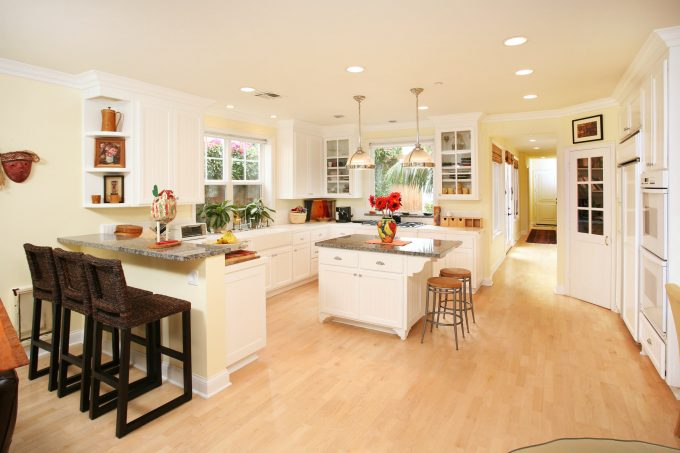 Custom Kitchen Islands With Granite Countertop And Wicker Bar Stools In Modern Kitchen With White Kitchen Cabinets And Under Cabinet Microwave Plus Crown Moulding Also Wood Tile Flooring