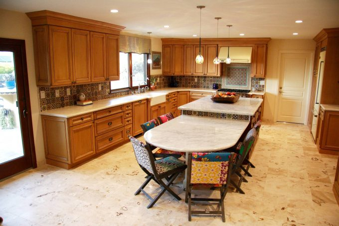 Custom Kitchen Islands With Marble Countertop And Decorative Dining Chairs In Mediterranean Kitchen With Tile Floors And Oak Cabinets Plus Mosaic Tile Backsplash Also Roman Blinds