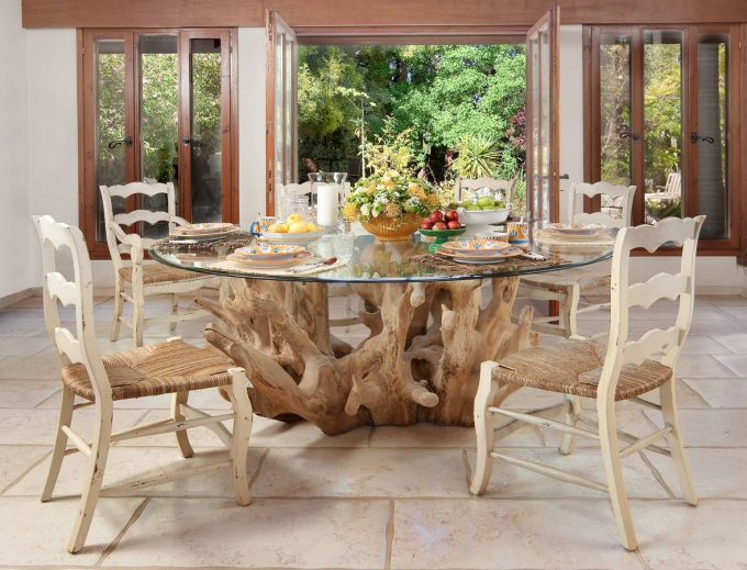 Driftwood Plus Round Glass Top For Dining Table On White Stone Flooring With Sisal Dining Chairs Plus Arrangement Flower And Dish Towels Also Plate With Fruits On Fruit Basket