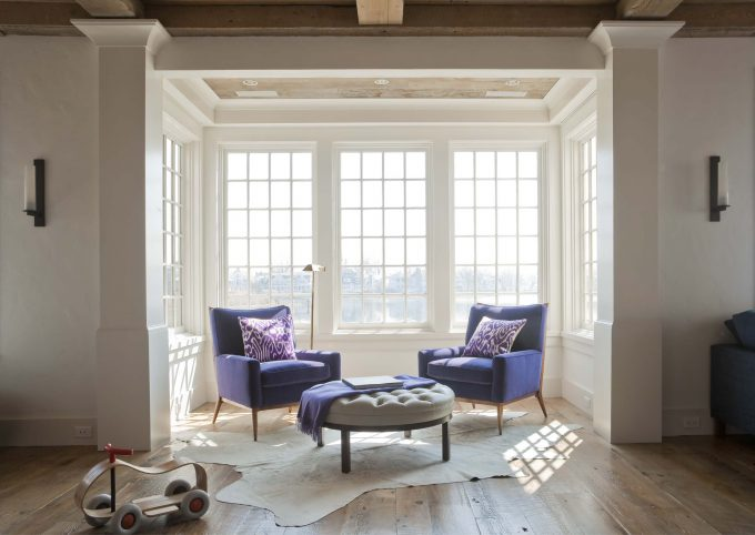 Eclectic Living Room With Wood Flooring Plus Animal Hide Rug And Round Tufted Ottoman Also Purple Cushion On Purple Armchairs With Wood Ceiling Plus Recessed Lighting