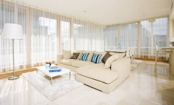 Great Modern Living Room With Modern Sectional Sofas Plus Decorative Pillows Also Chrome Coffee Table On Shag Rug With Crema Marfil Flooring Plus Floor Lamp Also Filmy Curtains For Large Windows