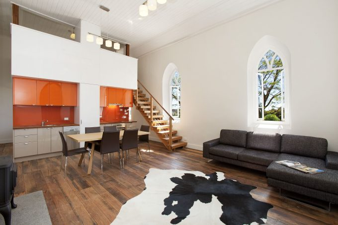 Industrial Kitchen With Arched Windows And Brown Dining Chairs Also High Gloss Cabinets And Cow Hide Area Rug Plus Wood Floor And Orange Cabinets