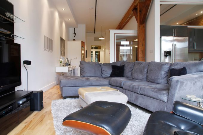 Industrial Living Room With Flat Tv On Unit Media Plus Recessed Lighting And Oversized Couches Also Ottoman Coffee Table On Shag Rug With Light Wood Flooring Plus Eames Chairs