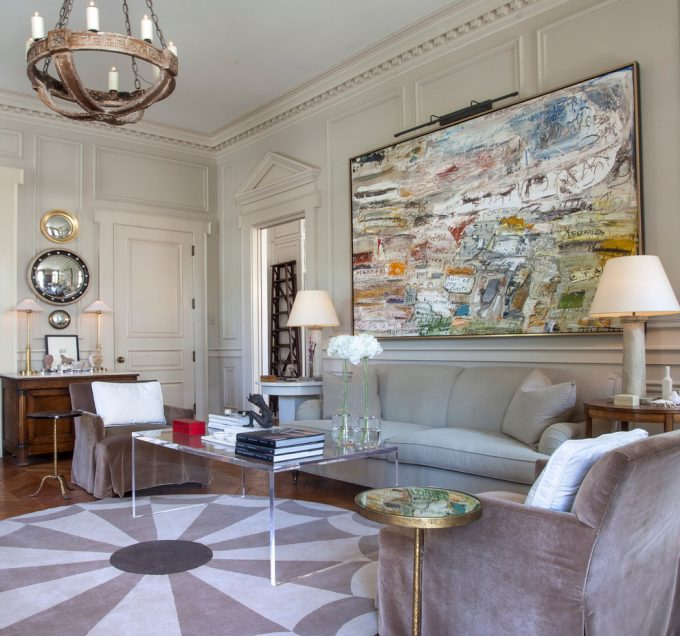 Marvelous Art On White Wall Plus Wainscoting And Crown Molding For Traditional Living Room With Wood Flooring Plus Round Rug And Gray Sofa Also Slipcover Chairs With Brass Round Side Table