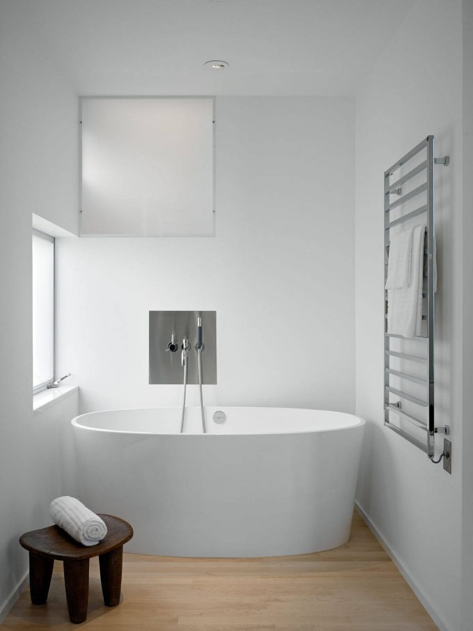 Modern Bathroom With Frosted Glass And Modern Fixtures Plus Natural Light And Ceiling Lighting With Towel Warmer On Stool Also Towel Rack And White Tub On Wood Flooring