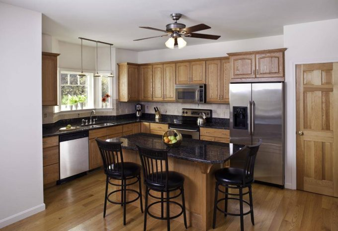 Modern Ceiling Fan On White Ceiling For Traditional Kitchen Ideas With Oak Cabinets And Black Granite Countertop On Kitchen Island Plus Black Stool Bar For Eat In Kitchen With Stainless Steel Appliances