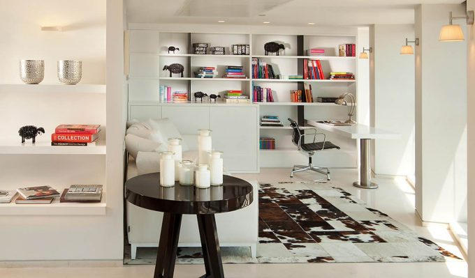 Modern Home Office With Bookshelves And Desk Lamp On White Desk Plus Office Chair With White Flooring Plus Cow Hide Rug And Wall Sconce Also Recessed Lighting