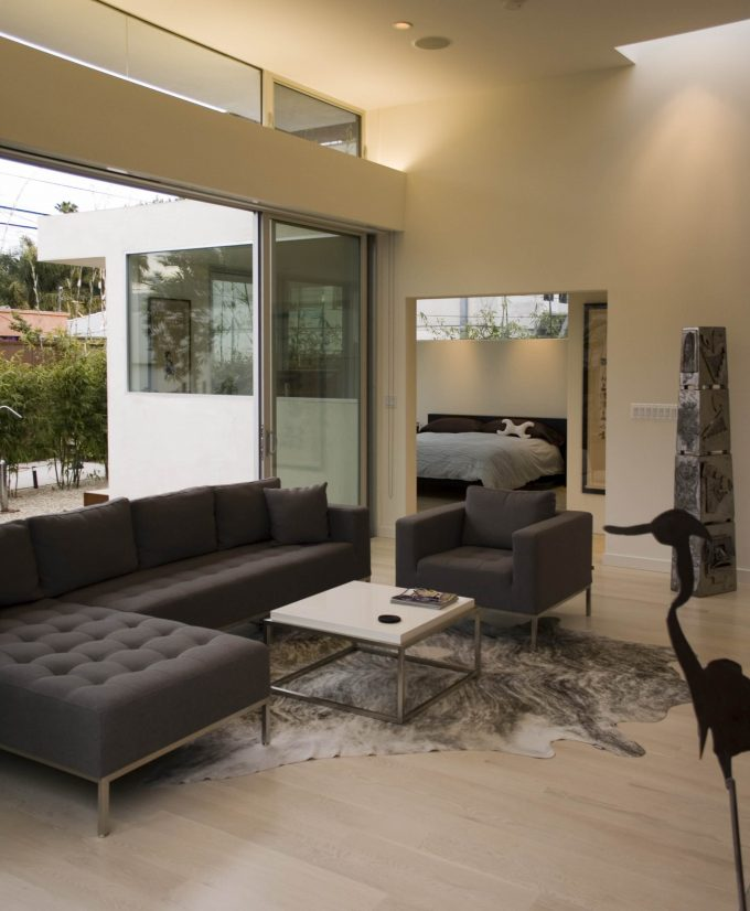 Modern Living Room With Light Wood Flooring Plus Cow Hide Rug And Modern Sectional Sofas Also Modern Coffee Table With Recessed Lighting And Brown Wall Plus Sculptures