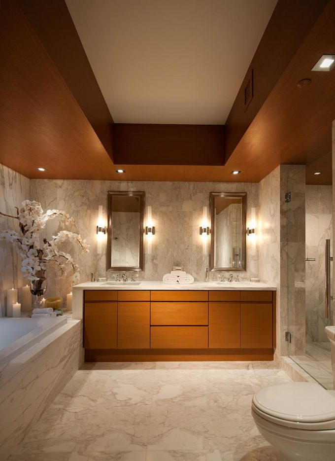 Modern Toilet With Marble Floor And Bathtub For Contemporary Bathroom Design With Glass Shower Panel And Mirrored Vanity Plus Wall Sconce Also Floral Arrangement