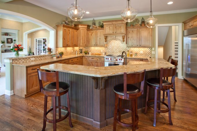 Oak Kitchen Cabinets With Tin Backsplash And Gas Stove In Traditional Kitchen With Custom Kitchen Islands And Kitchen Bar Stools Plus Quartz Countertop Also Dark Hardwood Floor