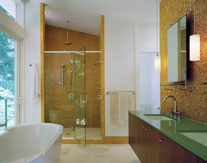 Sloped Ceiling And Orange Mosaic Tile Wall In Glass Shower Room With Rain Shower Head And Glass Countertops Plus Sink Also Wall Mirror And Pendant Lighting For Small Bathroom Remodel Ideas