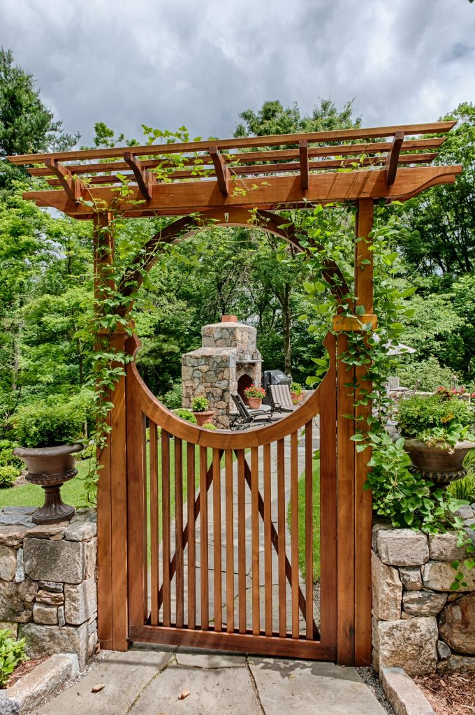 Stone Fence With Wooden Gates And Stone Walkway For Traditional Landscape Design With Outdoor Fireplaces And Outdoor Furniture Plus Lounge Chairs Also Potted Plants