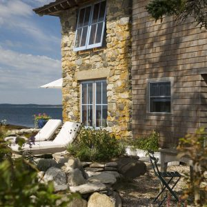 Stone Wall For Wall Exterior In Coastal Cottage Plus Awning Windows Also Shingle Siding Wall With Outdoor Lounge Chairs For Relax In Waterfront Plus Boulders And Planter Also Potted Plant