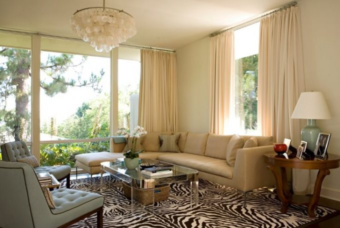Stunning Capiz Shell Chandelier In Traditional Family Room With Zebra Print Carpet Plus Lucite Coffee Table And Sectional Sofa With Green Table Lamp On Round Side Table And Window Treatments