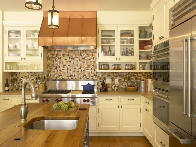 Stunning Glass Front Cabinets And Tile Backsplash Plus Copper Range Hoods And Kitchen Hardware Also Kitchen Island Plus Pendant Lighting With Stainless Steel Appliances And Wood Flooring