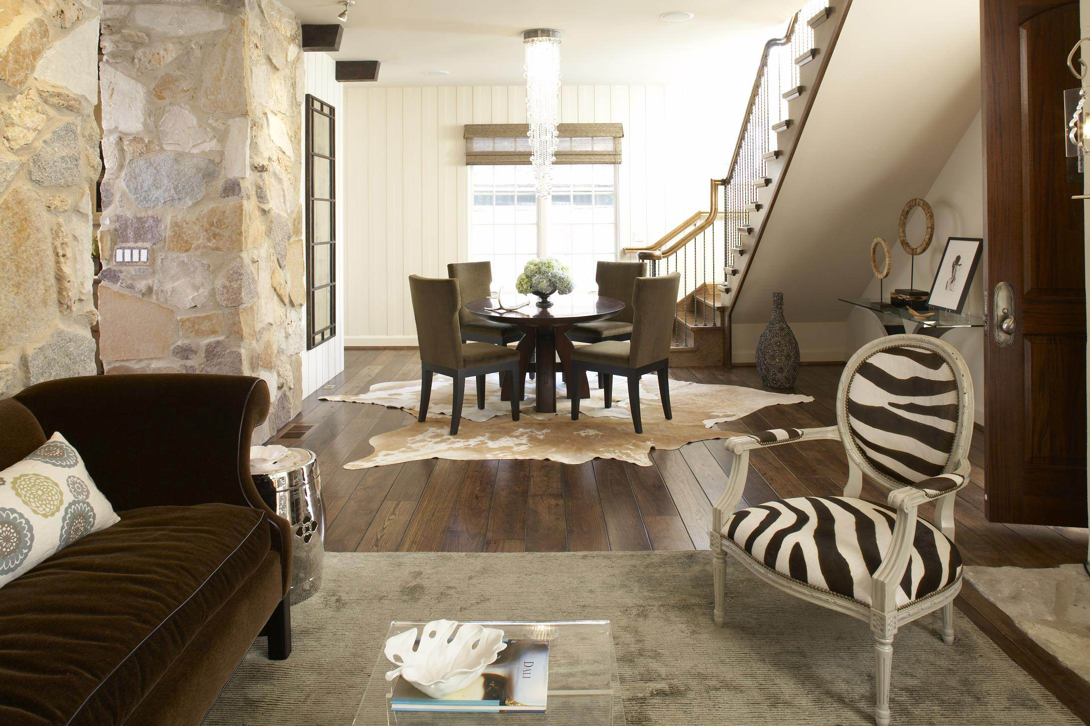 Traditional Family Room Designs With Stone Wall And Plank Wood Flooring Plus Cow Hide Rug For Area Dining With Glass Round Dining Table And Upholstered Dining Chairs Also Zebra Print