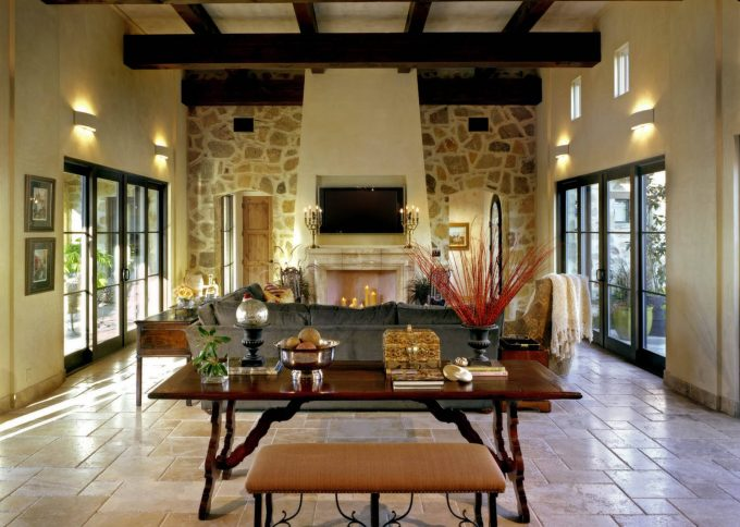 Travertine Tile Floor With Rustic Table And Living Room Bench In Mediterranean Living Room With Wall Sconce And Stone Wall Plus Tv Over Fireplace Also Ceiling Beams