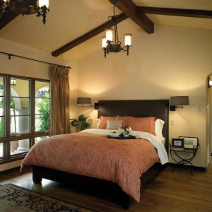 Tufted Bed With Ceiling Beams And Black Chandelier For Mediterranean Bedroom Design With Wall Sconce And Contemporary Curtain Plus Bedside Table Also Feizy Rug