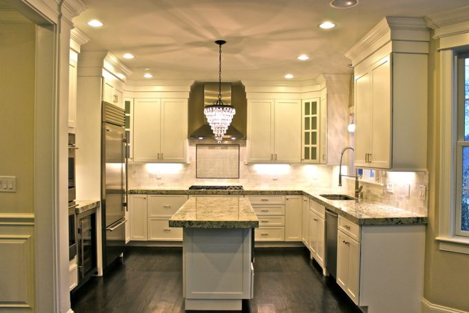 White Ice Granite With Crystal Chandelier Also Dark Wood Floors And White Kitchen Cabinets With Recessed Lighting Also Range Hood And Crown Molding Plus Kitchen Faucet For Contemporary Kitchen